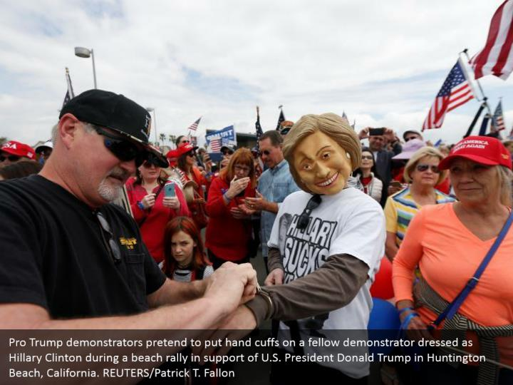 Pro Trump demonstrators pretend to put hand cuffs on a fellow demonstrator dressed as Hillary Clinton during a beach rally in support of U.S. President Donald Trump in Huntington Beach, California. REUTERS/Patrick T. Fallon