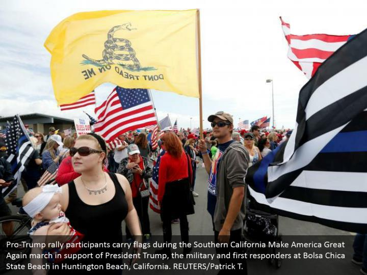 Pro-Trump rally participants carry flags during the Southern California Make America Great Again march in support of President Trump, the military and first responders at Bolsa Chica State Beach in Huntington Beach, California. REUTERS/Patrick T.