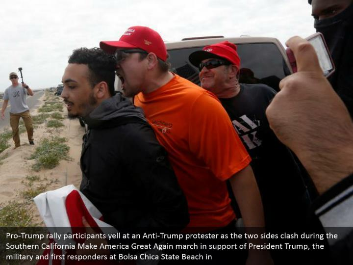 Pro-Trump rally participants yell at an Anti-Trump protester as the two sides clash during the Southern California Make America Great Again march in support of President Trump, the military and first responders at Bolsa Chica State Beach in