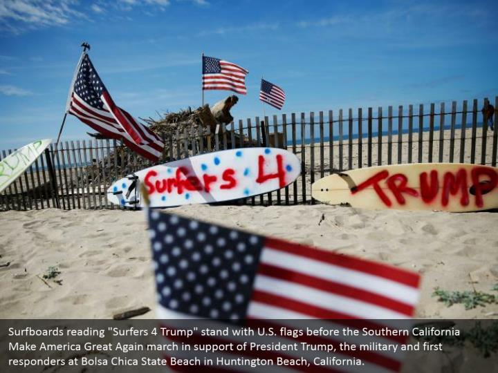 """Surfboards reading """"Surfers 4 Trump"""" stand with U.S. flags before the Southern California Make America Great Again march in support of President Trump, the military and first responders at Bolsa Chica State Beach in Huntington Beach, California."""