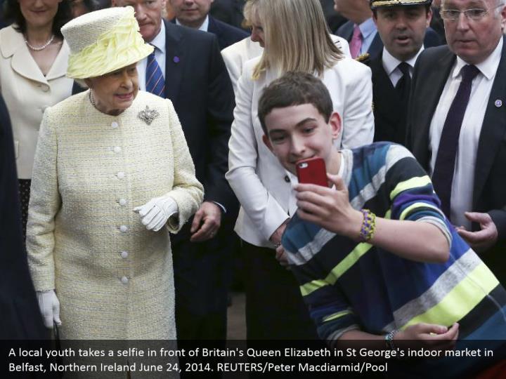 A local youth takes a selfie in front of Britain's Queen Elizabeth in St George's indoor market in Belfast, Northern Ireland June 24, 2014. REUTERS/Peter Macdiarmid/Pool