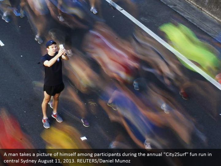 """A man takes a picture of himself among participants during the annual """"City2Surf"""" fun run in central Sydney August 11, 2013. REUTERS/Daniel Munoz"""