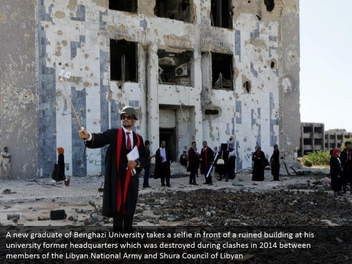 A new graduate of Benghazi University takes a selfie in front of a ruined building at his university former headquarters which was destroyed during clashes in 2014 between members of the Libyan National Army and Shura Council of Libyan