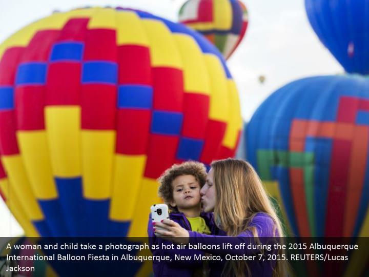 A woman and child take a photograph as hot air balloons lift off during the 2015 Albuquerque International Balloon Fiesta in Albuquerque, New Mexico, October 7, 2015. REUTERS/Lucas Jackson