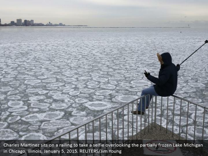 Charles Martinez sits on a railing to take a selfie overlooking the partially frozen Lake Michigan in Chicago, Illinois, January 5, 2015. REUTERS/Jim Young