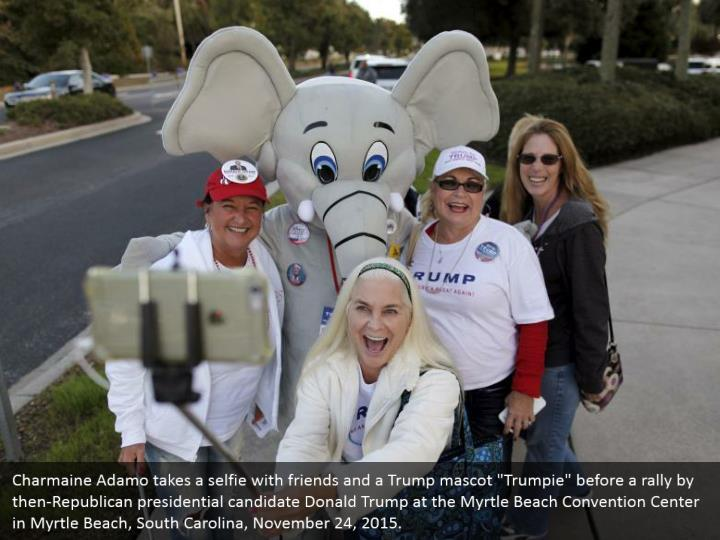 """Charmaine Adamo takes a selfie with friends and a Trump mascot """"Trumpie"""" before a rally by then-Republican presidential candidate Donald Trump at the Myrtle Beach Convention Center in Myrtle Beach, South Carolina, November 24, 2015."""