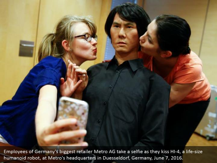 Employees of Germany's biggest retailer Metro AG take a selfie as they kiss HI-4, a life-size humanoid robot, at Metro's headquarters in Duesseldorf, Germany, June 7, 2016.