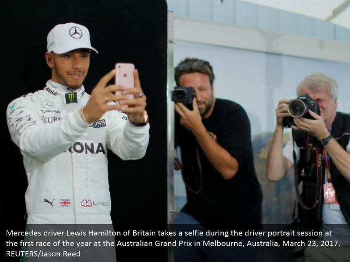 Mercedes driver Lewis Hamilton of Britain takes a selfie during the driver portrait session at the first race of the year at the Australian Grand Prix in Melbourne, Australia, March 23, 2017. REUTERS/Jason Reed