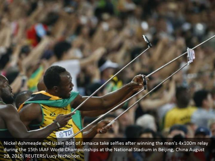 Nickel Ashmeade and Usain Bolt of Jamaica take selfies after winning the men's 4x100m relay during the 15th IAAF World Championships at the National Stadium in Beijing, China August 29, 2015. REUTERS/Lucy Nicholson