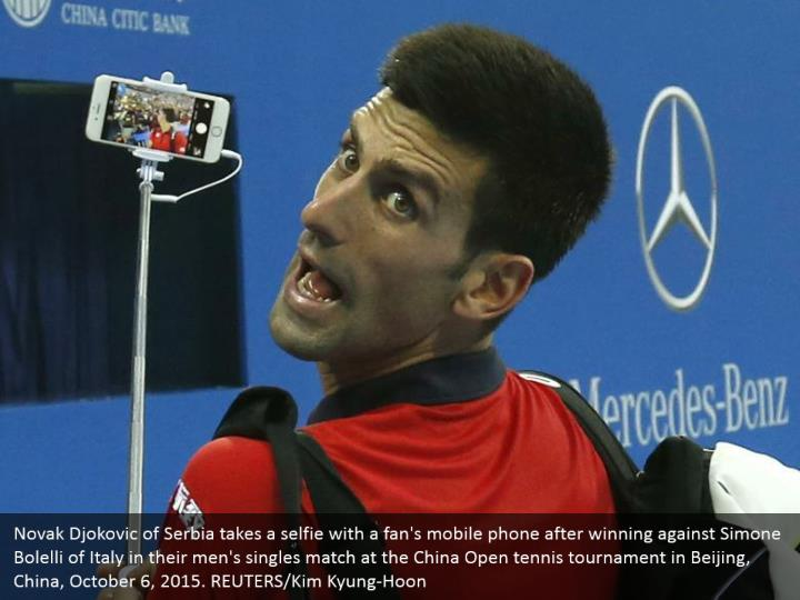 Novak Djokovic of Serbia takes a selfie with a fan's mobile phone after winning against Simone Bolelli of Italy in their men's singles match at the China Open tennis tournament in Beijing, China, October 6, 2015. REUTERS/Kim Kyung-Hoon