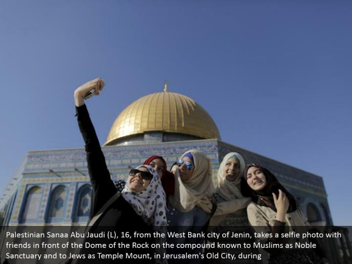 Palestinian Sanaa Abu Jaudi (L), 16, from the West Bank city of Jenin, takes a selfie photo with friends in front of the Dome of the Rock on the compound known to Muslims as Noble Sanctuary and to Jews as Temple Mount, in Jerusalem's Old City, during