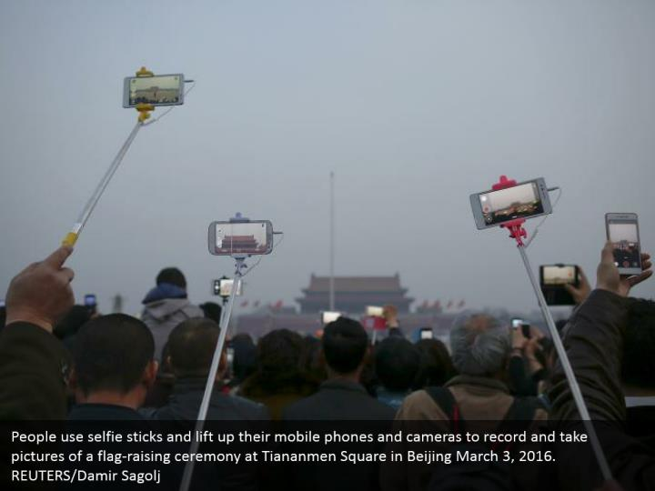 People use selfie sticks and lift up their mobile phones and cameras to record and take pictures of a flag-raising ceremony at Tiananmen Square in Beijing March 3, 2016. REUTERS/Damir Sagolj