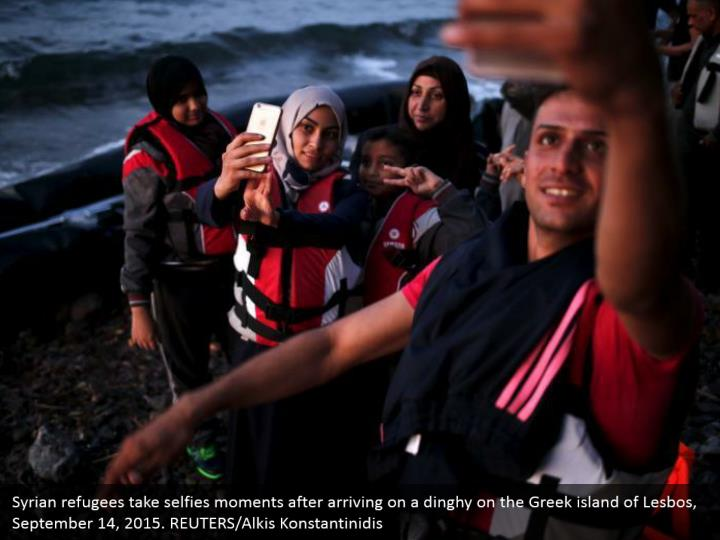 Syrian refugees take selfies moments after arriving on a dinghy on the Greek island of Lesbos, September 14, 2015. REUTERS/Alkis Konstantinidis