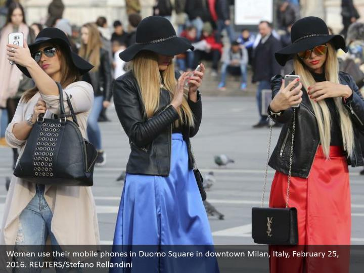 Women use their mobile phones in Duomo Square in downtown Milan, Italy, February 25, 2016. REUTERS/Stefano Rellandini