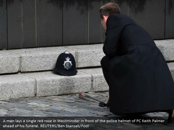A man lays a single red rose in Westminster in front of the police helmet of PC Keith Palmer ahead of his funeral. REUTERS/Ben Stansall/Pool