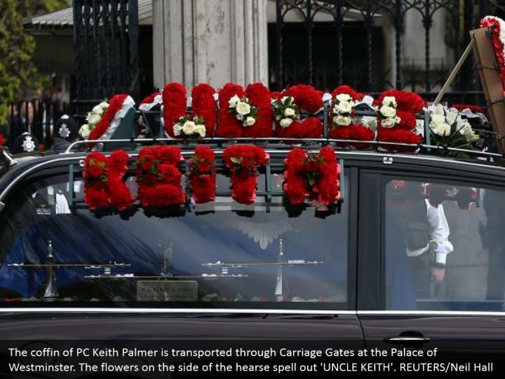 The coffin of PC Keith Palmer is transported through Carriage Gates at the Palace of Westminster. The flowers on the side of the hearse spell out 'UNCLE KEITH'. REUTERS/Neil Hall