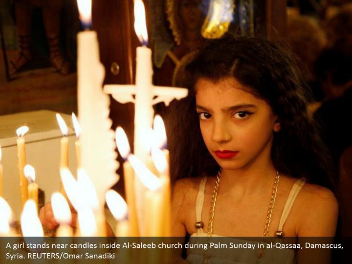 A girl stands near candles inside Al-Saleeb church during Palm Sunday in al-Qassaa, Damascus, Syria. REUTERS/Omar Sanadiki