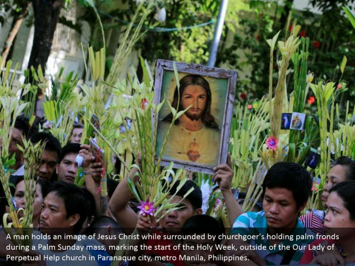 A man holds an image of Jesus Christ while surrounded by churchgoer's holding palm fronds during a Palm Sunday mass, marking the start of the Holy Week, outside of the Our Lady of Perpetual Help church in Paranaque city, metro Manila, Philippines.