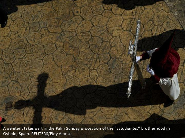 """A penitent takes part in the Palm Sunday procession of the """"Estudiantes"""" brotherhood in Oviedo, Spain. REUTERS/Eloy Alonso"""