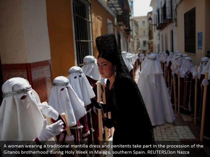 A woman wearing a traditional mantilla dress and penitents take part in the procession of the Gitanos brotherhood during Holy Week in Malaga, southern Spain. REUTERS/Jon Nazca