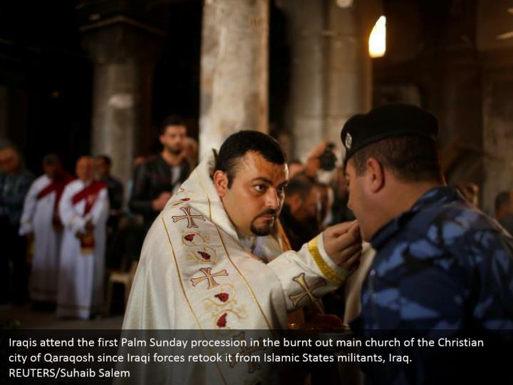 Iraqis attend the first Palm Sunday procession in the burnt out main church of the Christian city of Qaraqosh since Iraqi forces retook it from Islamic States militants, Iraq. REUTERS/Suhaib Salem