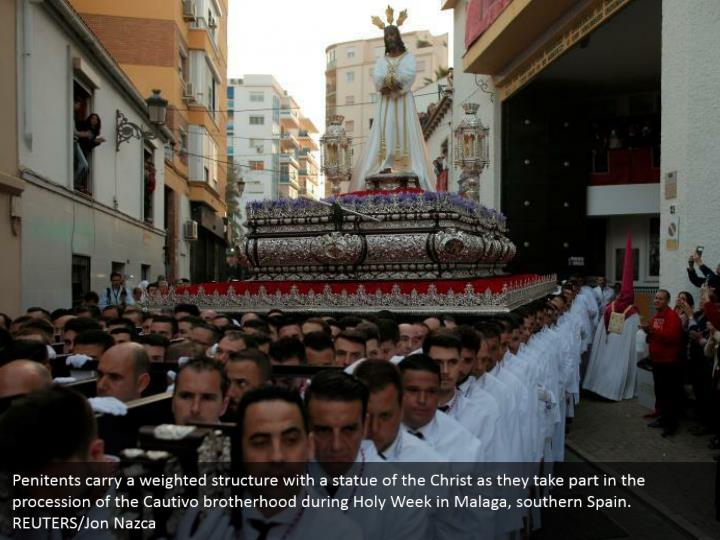 Penitents carry a weighted structure with a statue of the Christ as they take part in the procession of the Cautivo brotherhood during Holy Week in Malaga, southern Spain. REUTERS/Jon Nazca