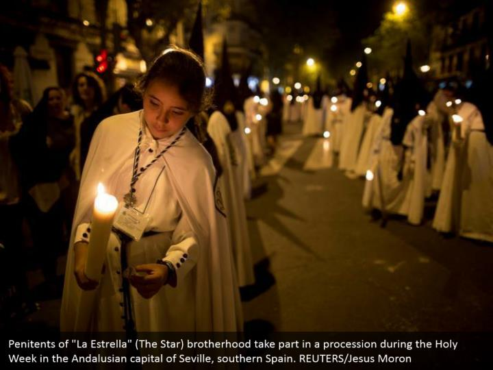 """Penitents of """"La Estrella"""" (The Star) brotherhood take part in a procession during the Holy Week in the Andalusian capital of Seville, southern Spain. REUTERS/Jesus Moron"""