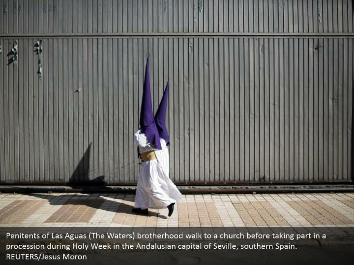 Penitents of Las Aguas (The Waters) brotherhood walk to a church before taking part in a procession during Holy Week in the Andalusian capital of Seville, southern Spain. REUTERS/Jesus Moron