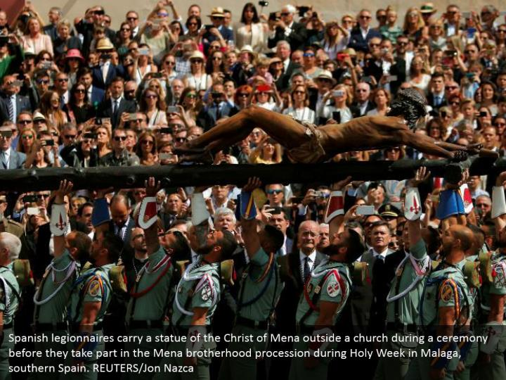 Spanish legionnaires carry a statue of the Christ of Mena outside a church during a ceremony before they take part in the Mena brotherhood procession during Holy Week in Malaga, southern Spain. REUTERS/Jon Nazca