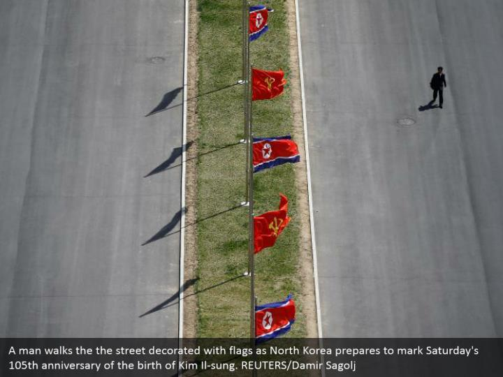 A man walks the the street decorated with flags as North Korea prepares to mark Saturday's 105th anniversary of the birth of Kim Il-sung. REUTERS/Damir Sagolj