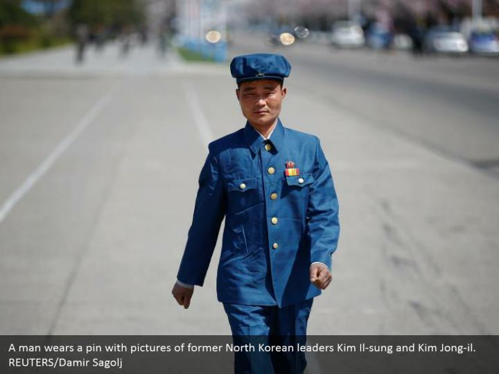 A man wears a pin with pictures of former North Korean leaders Kim Il-sung and Kim Jong-il. REUTERS/Damir Sagolj