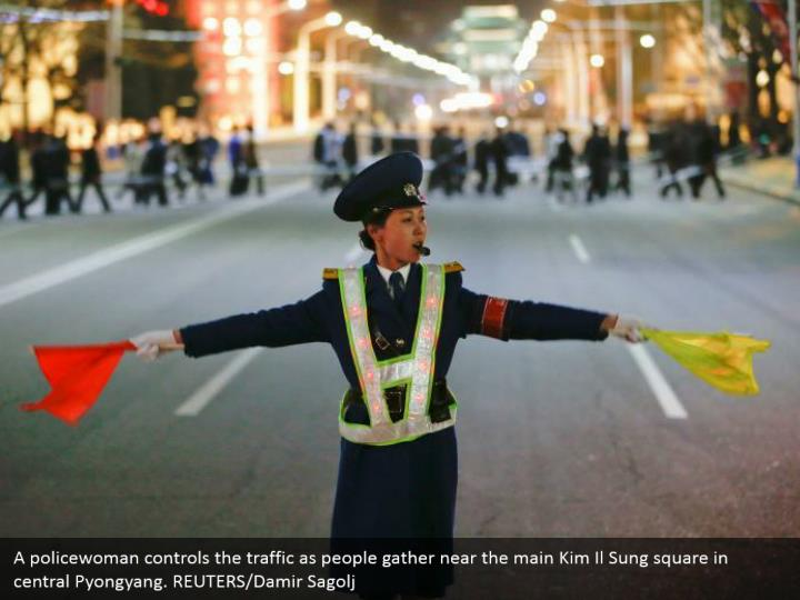 A policewoman controls the traffic as people gather near the main Kim Il Sung square in central Pyongyang. REUTERS/Damir Sagolj