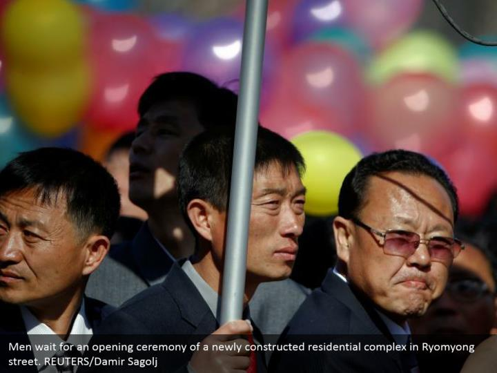Men wait for an opening ceremony of a newly constructed residential complex in Ryomyong street. REUTERS/Damir Sagolj