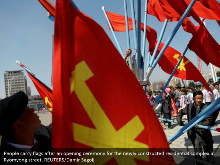 People carry flags after an opening ceremony for the newly constructed residential complex in Ryomyong street. REUTERS/Damir Sagolj