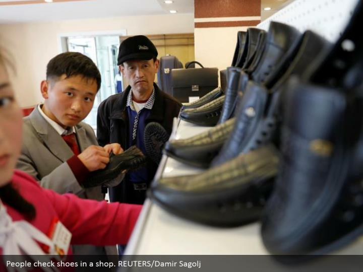 People check shoes in a shop. REUTERS/Damir Sagolj