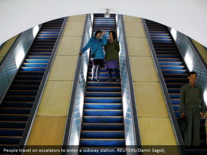 People travel on escalators to enter a subway station. REUTERS/Damir Sagolj