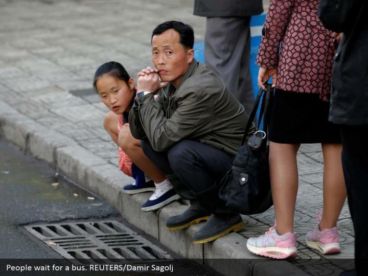 People wait for a bus. REUTERS/Damir Sagolj