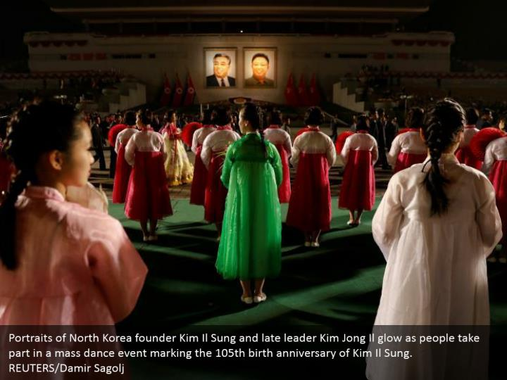 Portraits of North Korea founder Kim Il Sung and late leader Kim Jong Il glow as people take part in a mass dance event marking the 105th birth anniversary of Kim Il Sung. REUTERS/Damir Sagolj