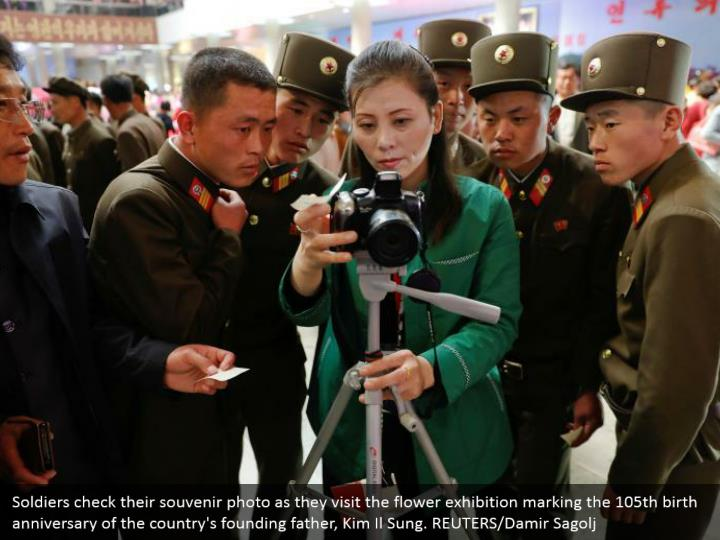 Soldiers check their souvenir photo as they visit the flower exhibition marking the 105th birth anniversary of the country's founding father, Kim Il Sung. REUTERS/Damir Sagolj