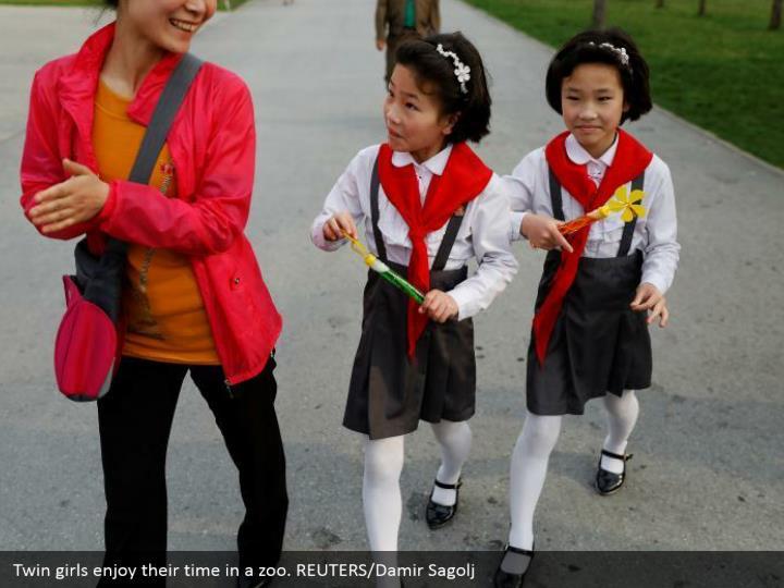 Twin girls enjoy their time in a zoo. REUTERS/Damir Sagolj