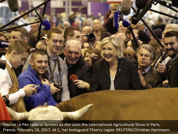 Marine Le Pen talks to farmers as she visits the International Agricultural Show in Paris, France, February 28, 2017. At C, her bodyguard Thierry Legier. REUTERS/Christian Hartmann