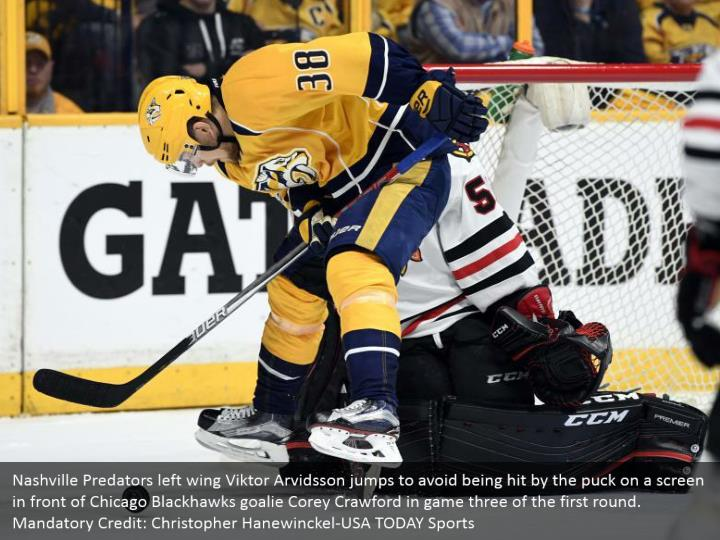 Nashville Predators left wing Viktor Arvidsson jumps to avoid being hit by the puck on a screen in front of Chicago Blackhawks goalie Corey Crawford in game three of the first round. Mandatory Credit: Christopher Hanewinckel-USA TODAY Sports