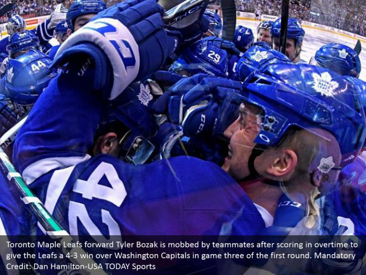 Toronto Maple Leafs forward Tyler Bozak is mobbed by teammates after scoring in overtime to give the Leafs a 4-3 win over Washington Capitals in game three of the first round. Mandatory Credit: Dan Hamilton-USA TODAY Sports