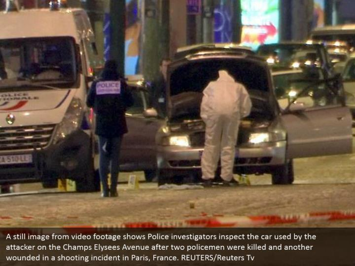 A still image from video footage shows Police investigators inspect the car used by the attacker on the Champs Elysees Avenue after two policemen were killed and another wounded in a shooting incident in Paris, France. REUTERS/Reuters Tv