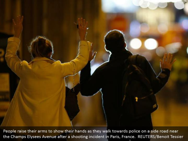 People raise their arms to show their hands as they walk towards police on a side road near the Champs Elysees Avenue after a shooting incident in Paris, France.  REUTERS/Benoit Tessier