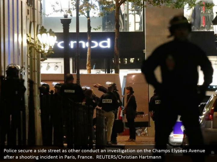 Police secure a side street as other conduct an investigation on the Champs Elysees Avenue after a shooting incident in Paris, France.  REUTERS/Christian Hartmann