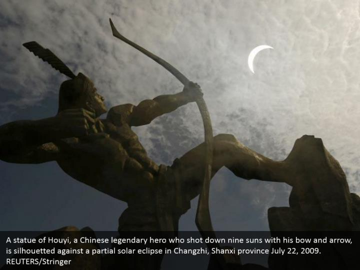 A statue of Houyi, a Chinese legendary hero who shot down nine suns with his bow and arrow, is silhouetted against a partial solar eclipse in Changzhi, Shanxi province July 22, 2009. REUTERS/Stringer