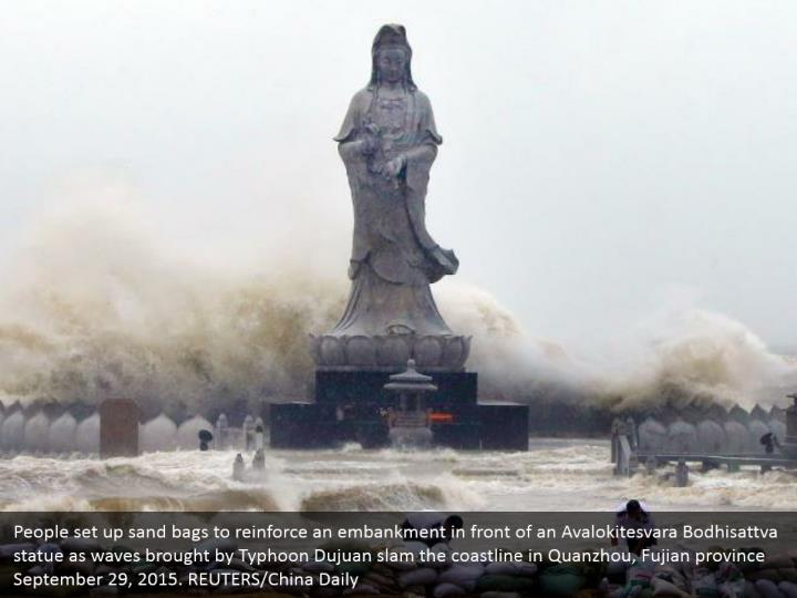 People set up sand bags to reinforce an embankment in front of an Avalokitesvara Bodhisattva statue as waves brought by Typhoon Dujuan slam the coastline in Quanzhou, Fujian province September 29, 2015. REUTERS/China Daily