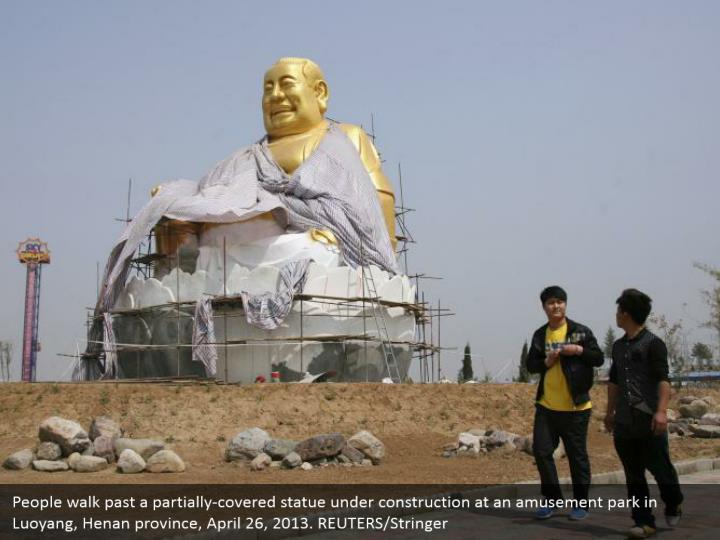 People walk past a partially-covered statue under construction at an amusement park in Luoyang, Henan province, April 26, 2013. REUTERS/Stringer