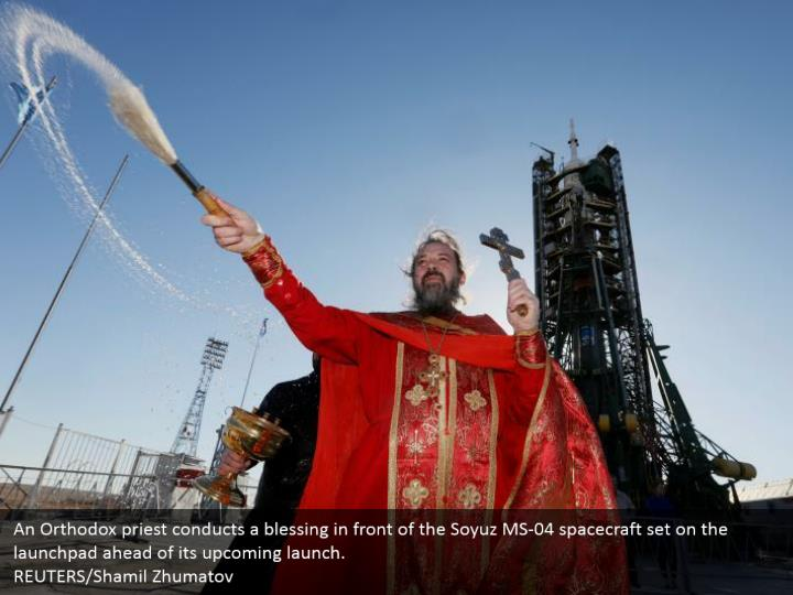 An Orthodox priest conducts a blessing in front of the Soyuz MS-04 spacecraft set on the launchpad ahead of its upcoming launch. REUTERS/Shamil Zhumatov